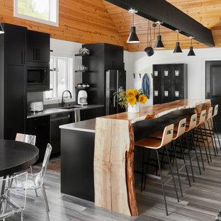 Diseño de cocina rústica, abierta, con fregadero bajoencimera, armarios con paneles lisos, puertas de armario negras, electrodomésticos de acero inoxidable, una isla, suelo multicolor y encimeras grises