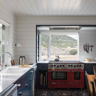 Inredning av ett lantligt vit vitt kök, med en undermonterad diskho, släta luckor, blå skåp, bänkskiva i kvarts, vitt stänkskydd, stänkskydd i trä, färgglada vitvaror, mörkt trägolv och brunt golv