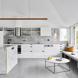 Beach style kitchen in Brisbane with flat-panel cabinets, white cabinets, grey splashback, concrete floors, with island, grey floor, grey benchtop and vaulted.