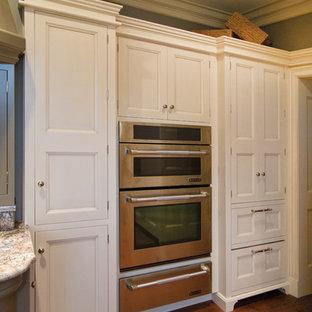 他の地域の大きいトラディショナルスタイルのおしゃれなキッチン (トリプルシンク、白いキャビネット、御影石カウンター、グレーのキッチンパネル、ガラスタイルのキッチンパネル、シルバーの調理設備の、無垢フローリング、アイランドなし、フラットパネル扉のキャビネット) の写真