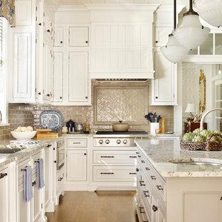 Ejemplo de cocina en L, tradicional, de tamaño medio, abierta, con fregadero bajoencimera, puertas de armario blancas, salpicadero beige, una isla, armarios con rebordes decorativos, encimera de granito, salpicadero de azulejos de porcelana, electrodomésticos con paneles y suelo de madera clara