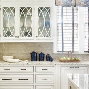 Modelo de cocina en L, clásica, de tamaño medio, abierta, con armarios con rebordes decorativos, puertas de armario blancas, encimera de granito, salpicadero beige, una isla, salpicadero de azulejos de porcelana, electrodomésticos con paneles, fregadero bajoencimera y suelo de madera clara