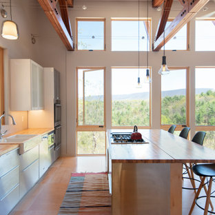 Photo of a modern eat-in kitchen with a farmhouse sink, stainless steel cabinets, wood benchtops, stainless steel appliances, plywood floors, with island and exposed beam.