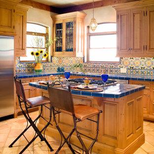 オースティンの地中海スタイルのおしゃれなキッチン (レイズドパネル扉のキャビネット、淡色木目調キャビネット、タイルカウンター、マルチカラーのキッチンパネル、シルバーの調理設備の、青いキッチンカウンター) の写真