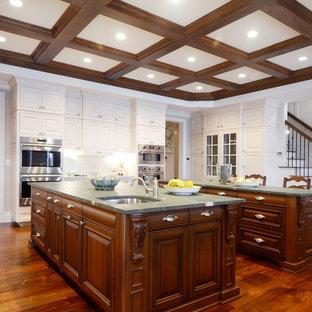Geschlossene, Geräumige Klassische Küche in U-Form mit Unterbauwaschbecken, profilierten Schrankfronten, weißen Schränken, Küchenrückwand in Weiß, Rückwand aus Porzellanfliesen, Küchengeräten aus Edelstahl, braunem Holzboden, zwei Kücheninseln, braunem Boden, Marmor-Arbeitsplatte und weißer Arbeitsplatte in Sonstige