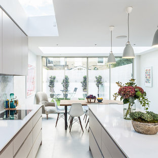 Design ideas for a contemporary kitchen/diner in London with a submerged sink, ceramic flooring, a breakfast bar, flat-panel cabinets, white cabinets and white floors.