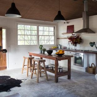 Mid-sized industrial single-wall eat-in kitchen in Melbourne with with island, a double-bowl sink, open cabinets, white cabinets, wood benchtops, white splashback, stainless steel appliances and concrete floors.