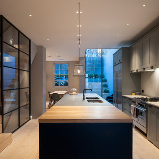Example of a transitional galley light wood floor eat-in kitchen design in London with a double-bowl sink, shaker cabinets, gray cabinets, wood countertops, stainless steel appliances and an island