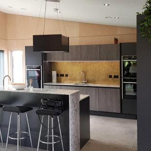 Große Moderne Küche in L-Form mit Unterbauwaschbecken, flächenbündigen Schrankfronten, hellbraunen Holzschränken, Küchenrückwand in Gelb, Elektrogeräten mit Frontblende, Porzellan-Bodenfliesen, Kücheninsel, grauem Boden und grauer Arbeitsplatte in Buckinghamshire