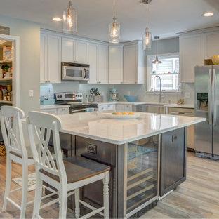 他の地域の中サイズのビーチスタイルのおしゃれなキッチン (エプロンフロントシンク、落し込みパネル扉のキャビネット、白いキャビネット、御影石カウンター、シルバーの調理設備の、クッションフロア、白いキッチンカウンター) の写真