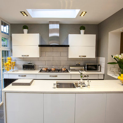 Inspiration for a small contemporary galley kitchen remodel in London with a double-bowl sink, flat-panel cabinets, white cabinets, white backsplash, subway tile backsplash and a peninsula