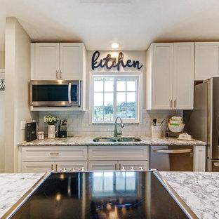 オーランドの中くらいのトランジショナルスタイルのおしゃれなキッチン (アンダーカウンターシンク、シェーカースタイル扉のキャビネット、白いキャビネット、クオーツストーンカウンター、白いキッチンパネル、磁器タイルのキッチンパネル、シルバーの調理設備、クッションフロア、グレーの床、ベージュのキッチンカウンター) の写真