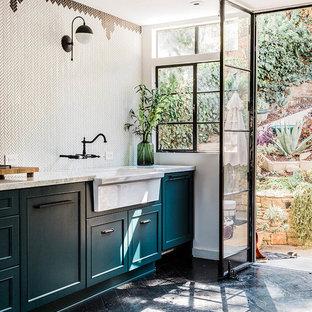 Geschlossene, Zweizeilige, Kleine Eklektische Küche mit Landhausspüle, flächenbündigen Schrankfronten, blauen Schränken, Marmor-Arbeitsplatte, Küchenrückwand in Weiß, Rückwand aus Keramikfliesen, Elektrogeräten mit Frontblende, dunklem Holzboden und weißer Arbeitsplatte in San Francisco