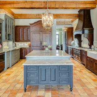 Idéer för ett mycket stort klassiskt kök, med en rustik diskho, bänkskiva i kvartsit, klinkergolv i terrakotta, skåp i mörkt trä, flerfärgad stänkskydd, svarta vitvaror, orange golv och flera köksöar