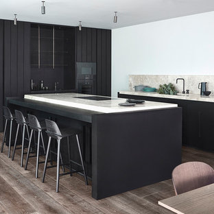 Inspiration for a contemporary u-shaped kitchen/diner in London with flat-panel cabinets, black cabinets, beige splashback, stone slab splashback, black appliances, dark hardwood flooring, an island, brown floors and beige worktops.