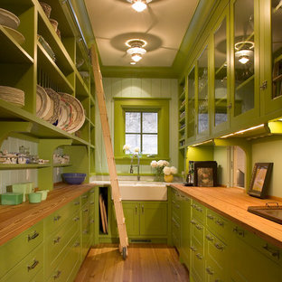 Inredning av ett lantligt kök, med en rustik diskho, luckor med glaspanel, gröna skåp, träbänkskiva, grönt stänkskydd, mellanmörkt trägolv och stänkskydd i glaskakel