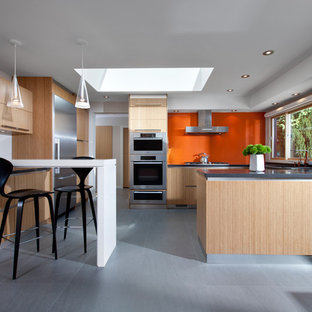 This is an example of a mid-sized midcentury u-shaped eat-in kitchen in Vancouver with orange splashback, glass sheet splashback, flat-panel cabinets, light wood cabinets, concrete benchtops, stainless steel appliances, an undermount sink, ceramic floors, a peninsula and grey floor.