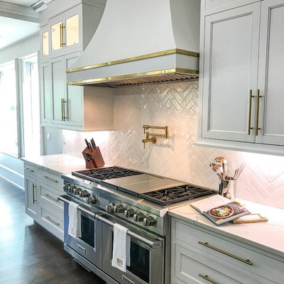 Inspiration for a huge transitional dark wood floor and brown floor kitchen remodel in Charlotte with a farmhouse sink, white cabinets, quartz countertops, white backsplash, ceramic backsplash, stainless steel appliances, an island, white countertops and recessed-panel cabinets