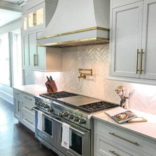Klassisk inredning av ett mycket stort vit vitt kök, med en rustik diskho, skåp i shakerstil, vita skåp, bänkskiva i kvarts, vitt stänkskydd, stänkskydd i keramik, rostfria vitvaror, mörkt trägolv, en köksö och brunt golv