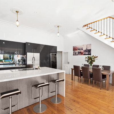 Trendy u-shaped light wood floor open concept kitchen photo in Melbourne with a drop-in sink, flat-panel cabinets, black cabinets, glass sheet backsplash, stainless steel appliances and a peninsula