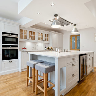This is an example of a medium sized traditional galley kitchen in Kent with shaker cabinets, white cabinets, black appliances, light hardwood flooring, an island, beige floors and white worktops.