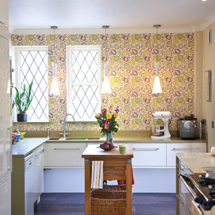 Design ideas for a large eclectic u-shaped kitchen in Cardiff with flat-panel cabinets, white cabinets, solid surface benchtops, porcelain floors, brown floor, an undermount sink and white appliances.