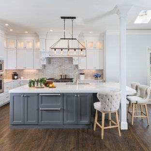 ボストンの広いトランジショナルスタイルのおしゃれなキッチン (アンダーカウンターシンク、白いキャビネット、大理石カウンター、グレーのキッチンパネル、セラミックタイルのキッチンパネル、シルバーの調理設備、茶色い床、シェーカースタイル扉のキャビネット、濃色無垢フローリング) の写真