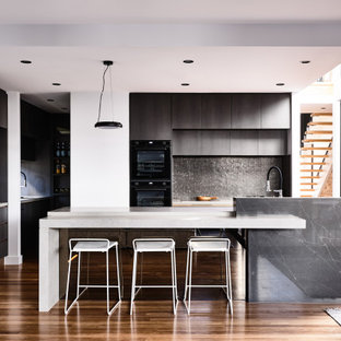 Photo of a contemporary u-shaped open plan kitchen in Brisbane with flat-panel cabinets, black cabinets, black splashback, mosaic tile splashback, black appliances, medium hardwood floors, with island, brown floor and white benchtop.