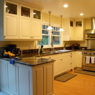 Design ideas for a small country galley separate kitchen in San Luis Obispo with an integrated sink, raised-panel cabinets, white cabinets, granite benchtops, stone slab splashback, stainless steel appliances, light hardwood floors and a peninsula.