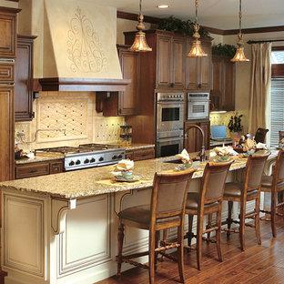 Eat-in kitchen - mid-sized mediterranean galley dark wood floor eat-in kitchen idea in Seattle with an undermount sink, raised-panel cabinets, dark wood cabinets, granite countertops, beige backsplash, stone tile backsplash, stainless steel appliances and an island