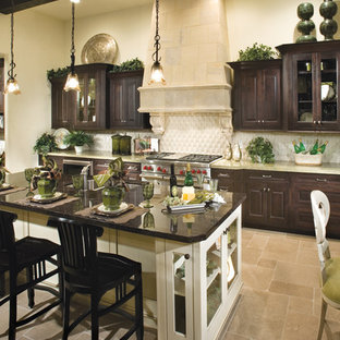 Inspiration for a large timeless galley ceramic floor eat-in kitchen remodel in Seattle with a double-bowl sink, raised-panel cabinets, dark wood cabinets, granite countertops, black backsplash, stone tile backsplash, stainless steel appliances and an island