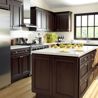 Eat-in kitchen - mid-sized transitional l-shaped light wood floor eat-in kitchen idea in Seattle with a double-bowl sink, recessed-panel cabinets, dark wood cabinets, quartz countertops, white backsplash, porcelain backsplash, stainless steel appliances and an island