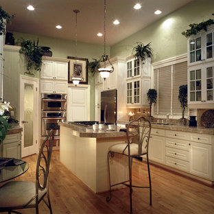 Example of a mid-sized tuscan l-shaped light wood floor eat-in kitchen design in Seattle with a double-bowl sink, raised-panel cabinets, white cabinets, granite countertops, multicolored backsplash, stone slab backsplash, stainless steel appliances and an island
