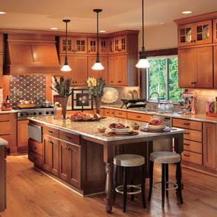 Inspiration for a large timeless u-shaped medium tone wood floor open concept kitchen remodel in Seattle with a double-bowl sink, shaker cabinets, medium tone wood cabinets, granite countertops, brown backsplash, stone tile backsplash, stainless steel appliances and an island