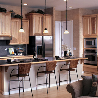 Open concept kitchen - mid-sized l-shaped light wood floor open concept kitchen idea in Seattle with a double-bowl sink, raised-panel cabinets, light wood cabinets, solid surface countertops, black backsplash, ceramic backsplash, stainless steel appliances and an island