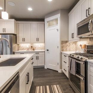 Offene, Große Klassische Küche in L-Form mit Unterbauwaschbecken, Schrankfronten im Shaker-Stil, weißen Schränken, Küchenrückwand in Braun, Küchengeräten aus Edelstahl, dunklem Holzboden, Kücheninsel, Quarzwerkstein-Arbeitsplatte, Rückwand aus Mosaikfliesen und braunem Boden in Salt Lake City