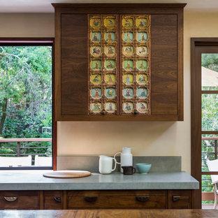 サンフランシスコの大きいトランジショナルスタイルのおしゃれなアイランドキッチン (ドロップインシンク、フラットパネル扉のキャビネット、中間色木目調キャビネット、木材カウンター、グレーのキッチンパネル、セメントタイルのキッチンパネル、シルバーの調理設備、淡色無垢フローリング、茶色い床) の写真