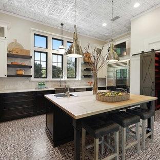 Geschlossene Klassische Küche in U-Form mit Landhausspüle, Schrankfronten im Shaker-Stil, dunklen Holzschränken, Küchenrückwand in Beige, bunten Elektrogeräten, Keramikboden, Kücheninsel, grauem Boden und weißer Arbeitsplatte in Austin
