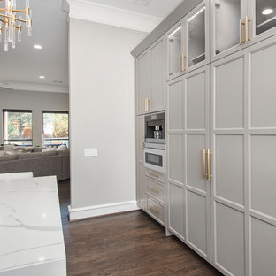 This is an example of a large contemporary u-shaped kitchen pantry in Dallas with a single-bowl sink, flat-panel cabinets, grey cabinets, engineered stone countertops, grey splashback, marble splashback, dark hardwood flooring, an island, brown floors, white worktops and integrated appliances.