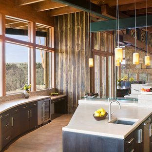 Large trendy u-shaped concrete floor enclosed kitchen photo in Denver with an undermount sink, flat-panel cabinets, dark wood cabinets, stainless steel appliances, concrete countertops, beige backsplash and an island