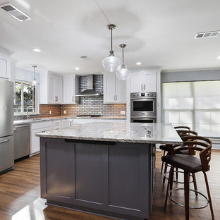 Large transitional open concept kitchen photos - Example of a large transitional u-shaped vinyl floor and brown floor open concept kitchen design in New Orleans with a single-bowl sink, shaker cabinets, white cabinets, granite countertops, gray backsplash, glass tile backsplash, stainless steel appliances, an island and white countertops