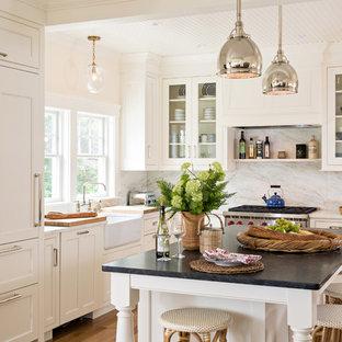 Свежая идея для дизайна: угловая кухня-гостиная среднего размера в стиле современная классика с раковиной в стиле кантри, фартуком из каменной плиты, островом, плоскими фасадами, белыми фасадами, мраморной столешницей, белым фартуком, техникой из нержавеющей стали, паркетным полом среднего тона и коричневым полом - отличное фото интерьера