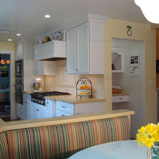 This is an example of a mid-sized eclectic galley separate kitchen in Los Angeles with a double-bowl sink, shaker cabinets, white cabinets, quartz benchtops, beige splashback, stone tile splashback, stainless steel appliances, medium hardwood floors and no island.
