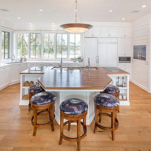 Cette image montre une cuisine marine en L avec un évier 3 bacs, un placard à porte shaker, des portes de placard blanches, un plan de travail en bois, une crédence en fenêtre, un électroménager encastrable, un sol en bois brun et un îlot central.
