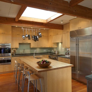 1950s l-shaped enclosed kitchen photo in Boston with flat-panel cabinets, medium tone wood cabinets, wood countertops, green backsplash and stainless steel appliances