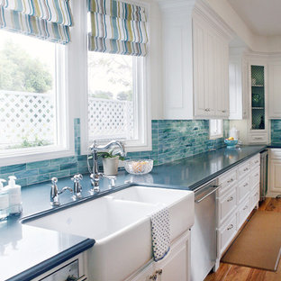 Mid-sized traditional single-wall open plan kitchen in Los Angeles with a farmhouse sink, raised-panel cabinets, white cabinets, stainless steel appliances, blue splashback, quartz benchtops, glass tile splashback, medium hardwood floors, with island and blue benchtop.