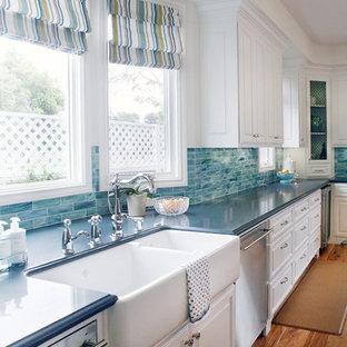 Einzeilige, Mittelgroße, Offene Klassische Küche mit Landhausspüle, profilierten Schrankfronten, weißen Schränken, Küchengeräten aus Edelstahl, Küchenrückwand in Blau, Quarzwerkstein-Arbeitsplatte, Rückwand aus Glasfliesen, braunem Holzboden, Kücheninsel und blauer Arbeitsplatte in Los Angeles