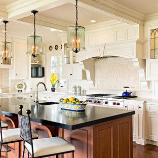Geräumige Klassische Wohnküche in U-Form mit profilierten Schrankfronten, Küchenrückwand in Beige, Küchengeräten aus Edelstahl, Kücheninsel, Unterbauwaschbecken, weißen Schränken, Speckstein-Arbeitsplatte, Rückwand aus Keramikfliesen und braunem Holzboden in Boston