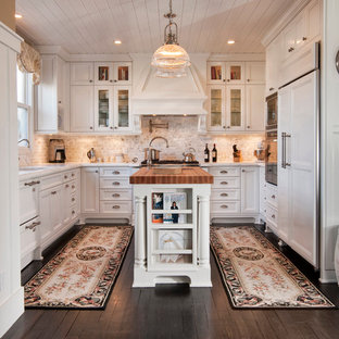 Modelo de cocina en U, clásica, cerrada, con fregadero bajoencimera, armarios tipo vitrina, puertas de armario blancas, salpicadero beige, electrodomésticos con paneles, una isla y salpicadero de travertino