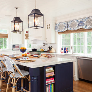 Beach style kitchen pictures - Kitchen - beach style single-wall medium tone wood floor kitchen idea in Boston with white cabinets, white backsplash, stainless steel appliances, an island, an undermount sink and shaker cabinets